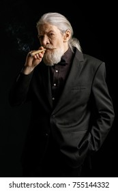 Aged wrinkled man standing against black background. Grey haired male smoking cigar.
