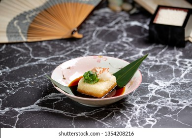 Agedashi tofu is crispy deep fried tofu served in flavorful dashi sauce and sprinkled with tuna flakes. Marble top