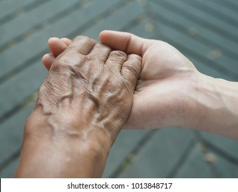 Ageing society (elderly care) or Mother Day or International Women Day concept with mother's hand in daughter's hand holding. (close up, selective focus)