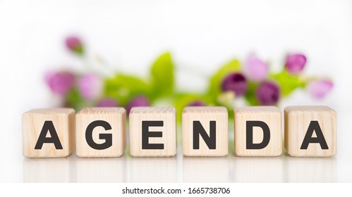 Agenda concept on wooden cubes with a bouquet of flowers