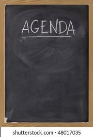 agenda - white chalk handwriting on blackboard with eraser smudges texture, copy space below