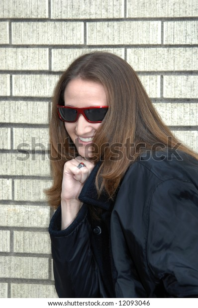 Agent in disguise.  Female teen poses with sunglasses and black coat.  Smiling.