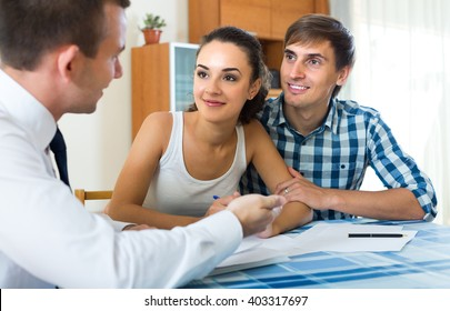 Agent explaining happy young couple details of insurance in home interior