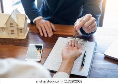 agent getting keys to customer new house, hand of real estate agent or realtor giving apartment key to receiving man after finish purchase deal agreement and sign contract, renting or buying home