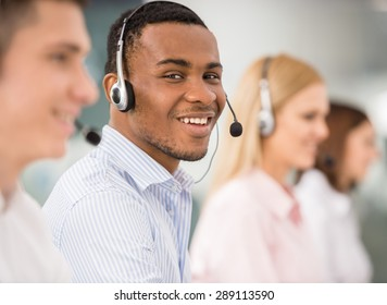 Agent smiling while working on his computer with colleagues next to him.