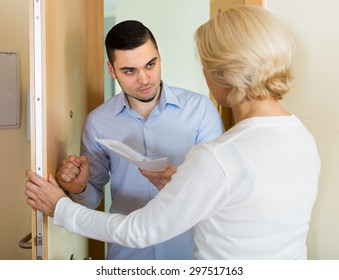 Agent trying to collect money from mature blonde housewife at home door. Focus on man