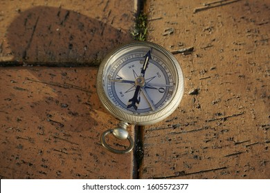 an ageold, silver compass used for the purpose of orientation