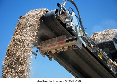aggregate production by mobile crusher. Conveyor belt of a working mobile crusher machine, close-up, with blown away by the wind white stone dust against a blue sky.