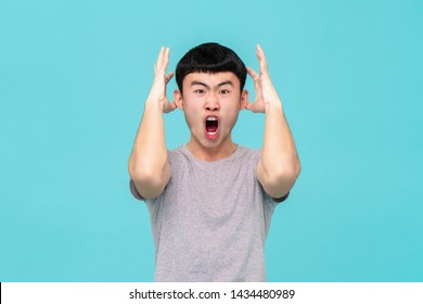 Aggressive angry young Asian man emotionally shouting isolated on light blue studio background