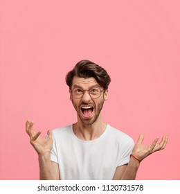 Aggressive attractive male with annoyed exppression, gestures angrily, yells, dressed in casual white t shirt, screams at friend, looks furious isolated on pink background. Negative emotions