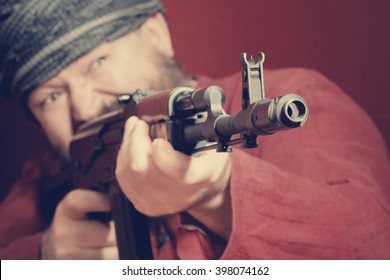 Aggressive bearded man in a red shirt with a gun aiming. Toned