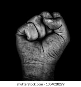 Aggressive black and white adult male clenched fist isolated on a black background. Socialism, communism, revolution, black power concept.