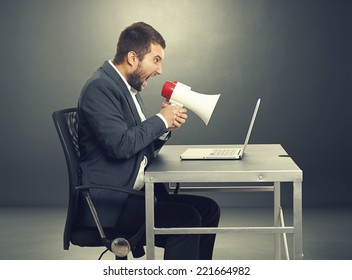 aggressive businessman screaming with megaphone and looking at laptop. photo in the dark room