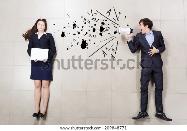 Aggressive businessman shouting at colleague with megaphone