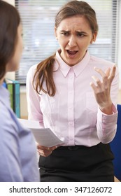Aggressive Businesswoman Shouting At Female Intern