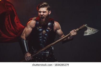 Aggressiver Kampf-Krieger mit Bart in schwarzer Rüstung, der seine zweihändige Axt auf dunklem Hintergrund hält.