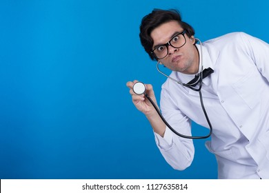 Aggressive doctor bending down raises the stethoscope listening to the heartbeats with angry face emotion on blue background.