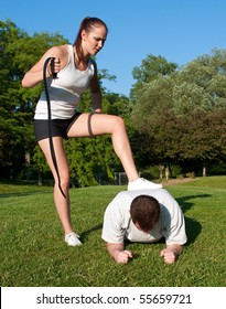 Aggressive female personal trainer whips man into shape with belt in hand and foot on his back