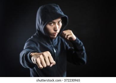 Aggressive fighter in hood while punching against black background