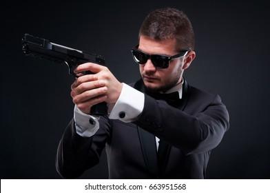 Aggressive gunman aiming pistol at his target on dark background