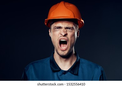 aggressive male engineer in an orange helmet and blue suit