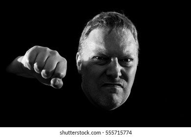 Aggressive man about to give a punch. Light setup used to make the face and eyes look dark