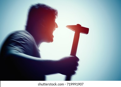 An aggressive man attacks with a hammer. Assault with a hammer. Hand with a hammer. Murder with a hammer.
