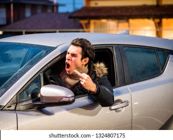 Aggressive man driving car and screaming away while showing obscene gesture on street