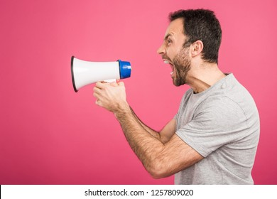 aggressive man shouting with megaphone, isolated on pink