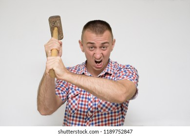 Aggressive man with a sledgehammer on a white background. Work concept