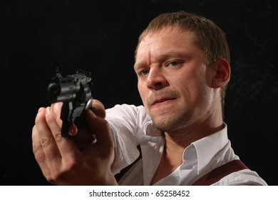 The aggressive man-gangster with a pistol. A portrait on a black background.