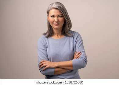 Aggressive Mongolian Woman with Gray Hair on a Gray Background. The Woman Has a Displeased Face. Her Arms are Crossed Before Her. Close Up Shoot.