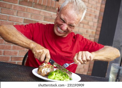 Aggressive senior man cutting strip steak served with loaded baked potato and broccoli at restaurant table