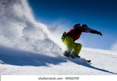 Aggressive skier making snow  powder while turning and skiing fast