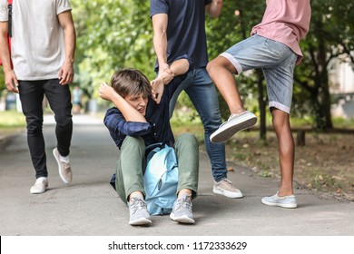 Aggressive teenagers bullying boy outdoors