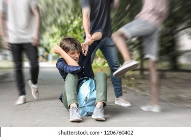 Aggressive teenagers bullying boy outdoors, view with motion blur effect