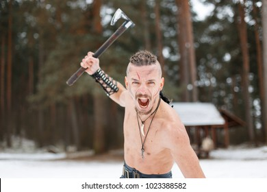 Aggressive Viking warrior man with a scar with an ax screaming outdoors