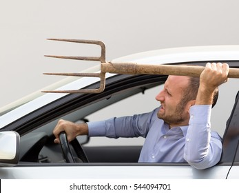 Aggressive and violent driver armed with a pitchfork. Copy space on the gray background.