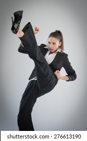 Aggressive woman in high heels kicking into the air. Martial Art Karate pose in the studio on grey background.