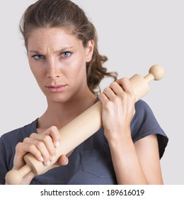 Aggressive woman holding a wooden rolling pin and looking at camera.