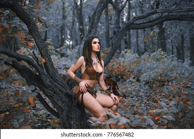 Aggressive-sexual wild girl, wanders in the jungle with a tamed bird. Artistic Photography