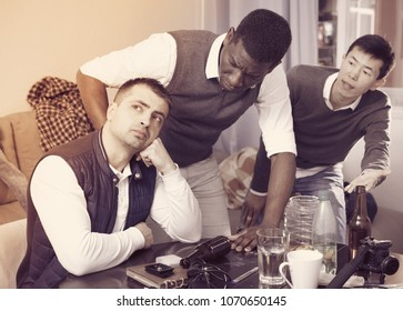 Aggrieved man dont speaking with two friends during quarrel indoors