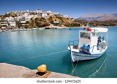 Agia Galini harbor in Crete Island (Greece) with a moored fishing boat in the foreground.