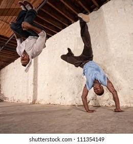 Agile capoeria martial artists perform acrobatic techniques