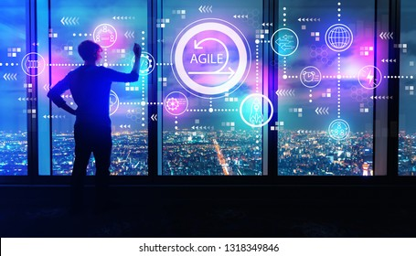 Agile concept with man writing on large windows high above a sprawling city at night