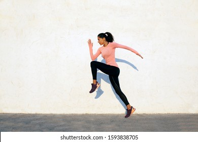 Agile and fit young woman jumping and running on the white concrete wall background, facing left, wearing black sport tights and pink shirt