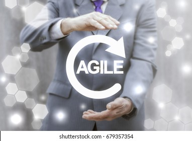 Agile Life Cycle. Agility software development. Flexible developing process. Technology, internet, business and marketing. Young man offers circular arrow agile word on virtual screen.