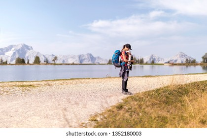 Agile Mother Hiking with her little cute baby in baby carrier