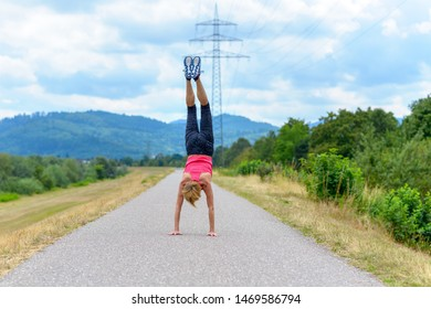 Agile woman doing a handstand on a quiet rural road with mountain backdrop in a concept of suppleness, health and an active lifestyle