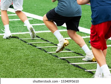 An agility ladder is on a green turf field with three young boys in cleats running through each leg.